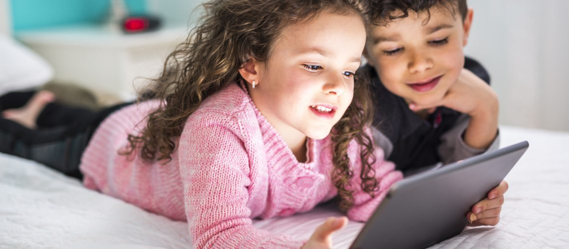 Two Cute brother and sister enjoying tablet at home